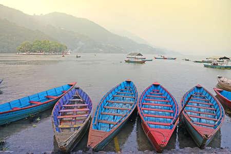 Colorful boats on the lake Phewa  Foggy morning in Pokhara, Nepal photo