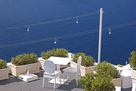 A cozy terrace with chairs and a table  View to the sea, Santorini, Greece photo