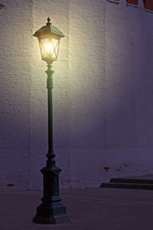 Old style street lamp in front of the wall of white brick photo