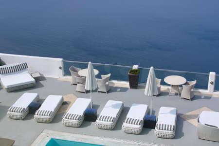 Sun beds and umbrellas at the poolside. Santorini, Greece photo