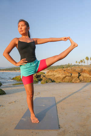 Beautiful asian woman doing yoga on the beach photo