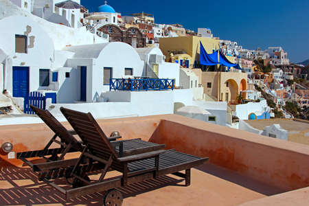 reclining chair: Terrace with deck chairs. Oia, Santorini, Greece Stock Photo
