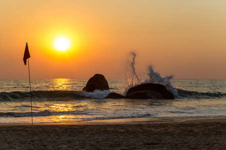 Sunset over the sea. Wave splashing on a rock. Goa, India 免版税图像