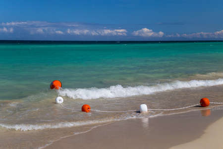 Safety float line on a soft wave in a white sand beach