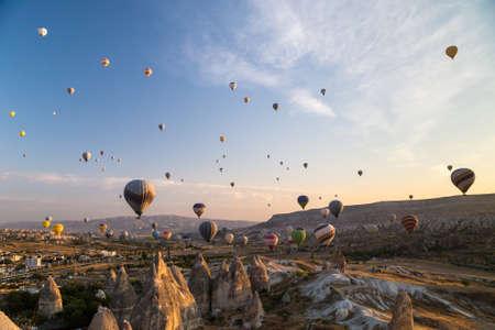 Hot air balloons flying at sunrise over rock formations in Cappadocia, Turkey 免版税图像
