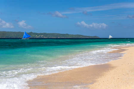 Small sailing boats passing by a white sand beach