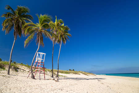Lifeguard chair under palm trees on a paradise beach. Cuba, the Caribbean