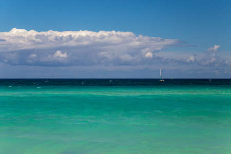 Background of turquoise sea, sky and clouds. Small sailboat at the horizon