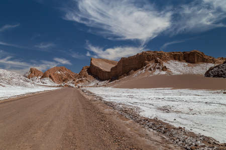 Road crossing Valle de la Luna. Dunes and rock formations covered with salt. Atacama, Chile
