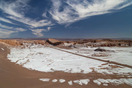Dunes and rock formations covered with dry salt in Valle de la Luna, Atacama, Chile