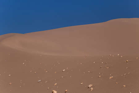 Big sand dune with stones on its slope