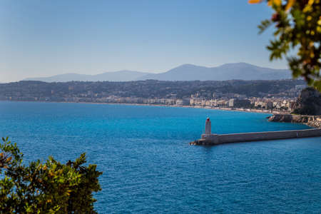 View to a lighhouse, a beach and a city. Nice, French Riviera 免版税图像