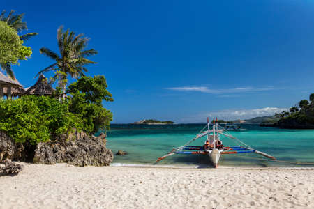 Traditional Philippine double-outrigger boat,  known as bangka, banca and paraw, at a pristine white sand beach 免版税图像