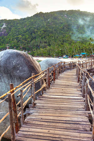 Small wooden bridge crossing rocks on the way to a beach. Koh Phangan, Thailand