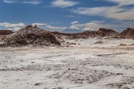 Rock formations covered with salt, volacanos on the background.  Valle de la Luna, Atacama, Chile