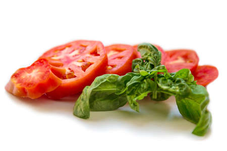 Sliced tomato with a basil leaf on white background 免版税图像