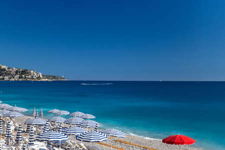 Beach in French Riviera. White sunbeds and umbrellas on the background of turquoise sea. Nice, Cote d'Azur 免版税图像
