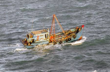 Fishing boat in a stormy sea Stock Photo