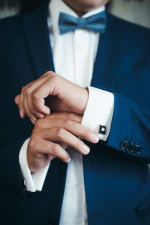 getting dressed: Cuff link, man is getting dressed