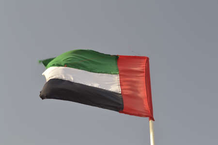 uncluttered: A United Arab Emirates flag flying against clean and tranquil sky. UAE celebrates its national day on 2nd December every year.