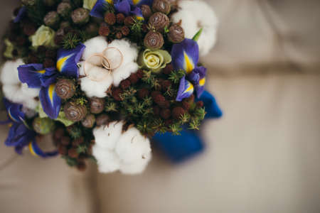 Beautiful winter wedding bouquet with cones, cotton and spruce branches. Bride holding a bridal bouquet. Stock Photo