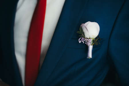 the groom in a blue suit and maroon butterfly