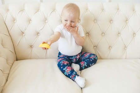 a little girl for the first time trying a lemon Stock Photo