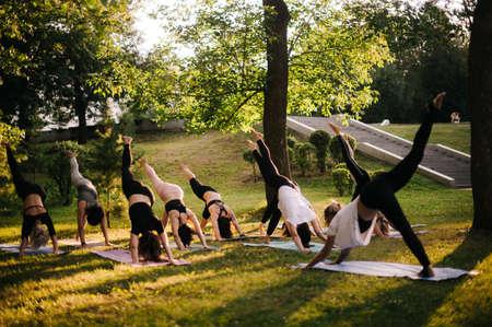 Group of flexible woman doing are yoga pose Adho Mukha Svanasana in city park