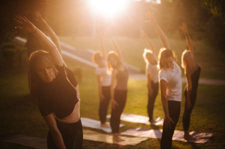 Group of women do yoga in city park on summer sunny sunrise or sunset