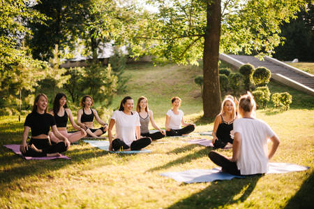 Group of smiling women prepare to meditation in park on summer sunny morning