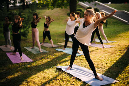Group of young women do yoga pose in city park on summer sunny morning under guidance of instructor
