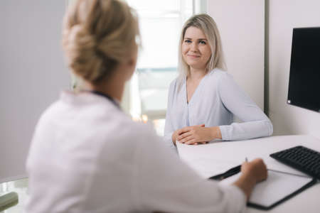 Healthcare and medical concept - doctor with young woman patient in hospital, at doctor appointment. Therapist female sitting at table and asks the patient questions