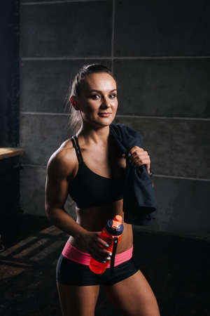 Portrait of muscular young woman with perfect athletic body in black sportswear with towel on shoulder, holding bottled water in hand on isolated balck background. Sporty female looking at camera