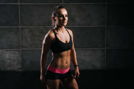 Muscular young woman with perfect athletic body in sports black bra is standing and posing on dark isolated background
