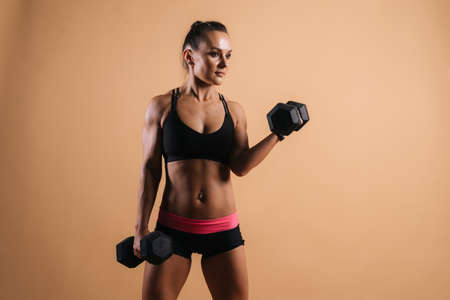 Portrait of muscular young woman with perfect athletic body in sports black bra posing with dumbbells. Shooting in professional studio on light pink red isolated background Stock Photo
