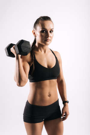 Sporty young woman with perfect muscular body in black sportswear is standing and holding dumbbell in strong hand on white isolated background. Muscular girl looking at camera