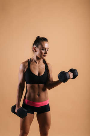 Fitness young woman with perfect muscular body in black sportswear is posing with two heavy dumbbells on red isolated background Stock Photo