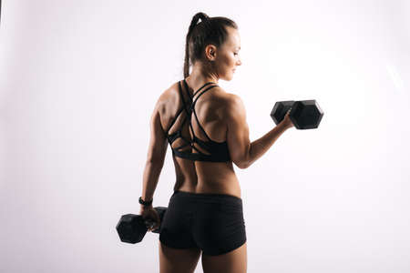 Back view portrait of fitness female with perfect muscular body in black sportswear. Working out with a heavy dumbbell on isolated white background