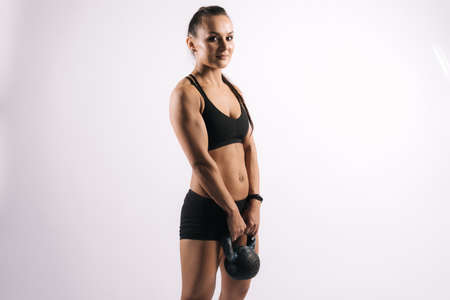 Muscular young woman with perfect athletic body in black sportswear is standing with 12 kg kettlebell and posing on white isolated background