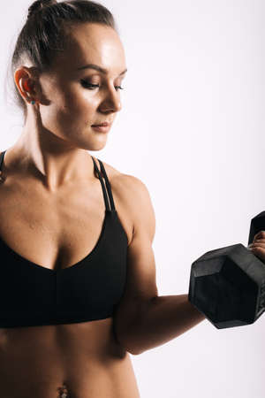Portrait of muscular young woman with perfect athletic body in sports black bra holding dumbbells in strong hand. Shooting in professional studio on white isolated background