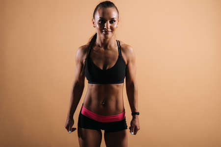 Beautiful fitness female with perfect muscular body in sports black bra goes forward to camera. Shooting in professional studio on red isolated background. Sporty beautiful female looking at camera Stock Photo
