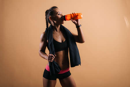 Portrait of muscular young woman with perfect athletic body in sports black bra drinking water on isolated light red background Stock Photo