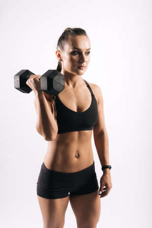 Sporty young woman with perfect muscular body in black sportswear is standing and holding dumbbell in strong hand on white isolated background