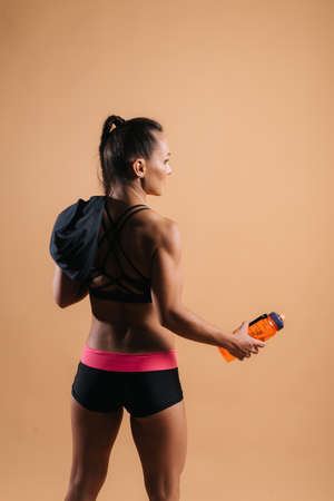 Back view portrait of sporty young woman with perfect muscular body in sports black bra with towel on her shoulder, is holding bottled water in her hand on isolated light red background