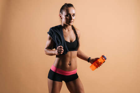 Beautiful fitness female with perfect muscular body in black sportswear with towel on her shoulder, is holding bottled water in her hand on isolated light red background Stock Photo