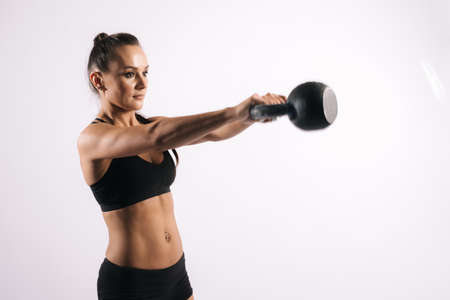 Sporty young woman with perfect muscular body in black sportswearis swinging kettlebell, on white isolated background Stock Photo - 129612224