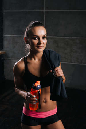 Muscular young woman with perfect athletic body with towel on shoulder, holding bottled water in hand on isolated balck background. Sporty muscular girl looking at the camera Stock Photo