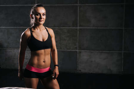 Sporty young woman with perfect muscular body in black sportswear is standing and posing on black isolated background Stock Photo