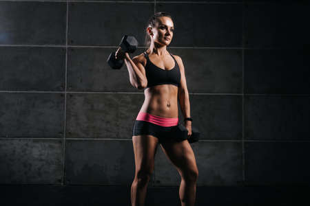 Young muscular woman bodybuilder with perfect athletic body in black sportswear is standing and holding dumbbell in strong hand on black background. Sporty beautiful female is looking away