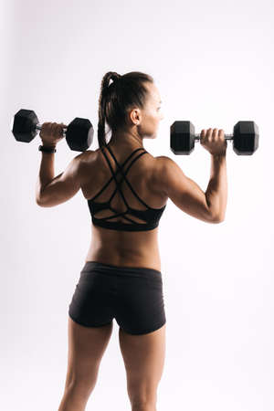 Back view portrait of young muscular woman bodybuilder with perfect athletic body in sports black bra. Sporty muscular girl is lifting dumbbells at shoulder level on isolated white background